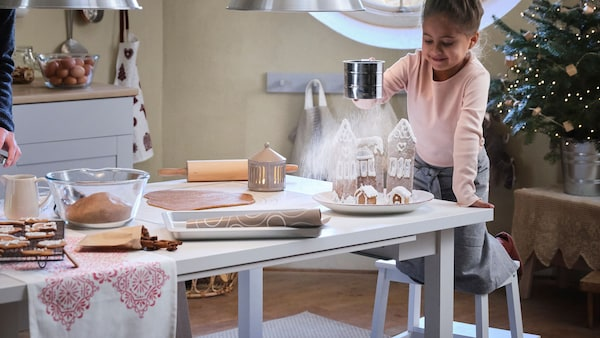 A boy and a girl festive baking in a traditional kitchen, at a  NORDVIKEN table. A VINTERSAGA gingerbread house, cookware and ingredients are on the table.