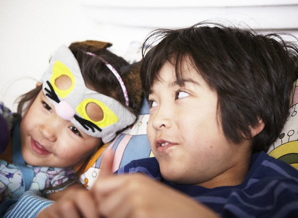A boy and a girl with a kitten mask on her forehead, sitting comfortably on a sofa while talking.
