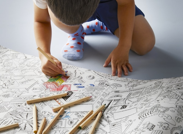 A boy coloring black-and-white drawings on a LUSTIGT coloring paper roll with MÅLA colored pencils.