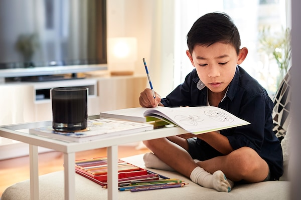 A boy is sitting on a sofa with his legs crossed. He is drawing in a book that is placed on a side table in front of him.