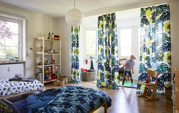A boy playing in a large bedroom with jungle-themed textiles.