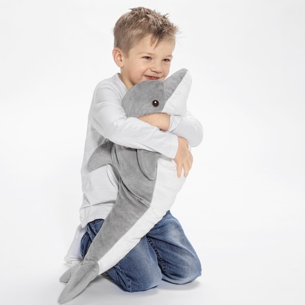 A boy playing with a soft toy.