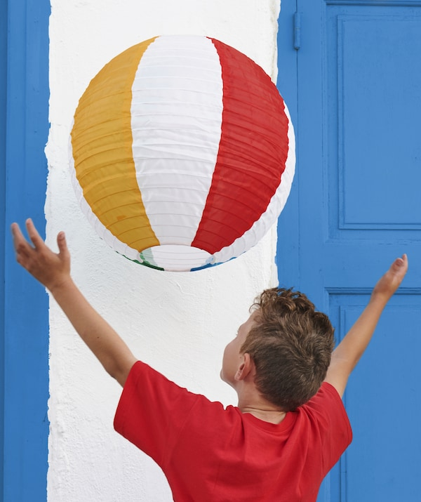 A boy reaching up to a striped hanging lantern.