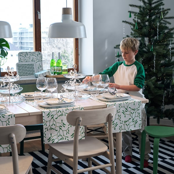 A boy sets a RÖNNINGE extendable table with glasses and other dinnerware, with a decorated tree in the background.