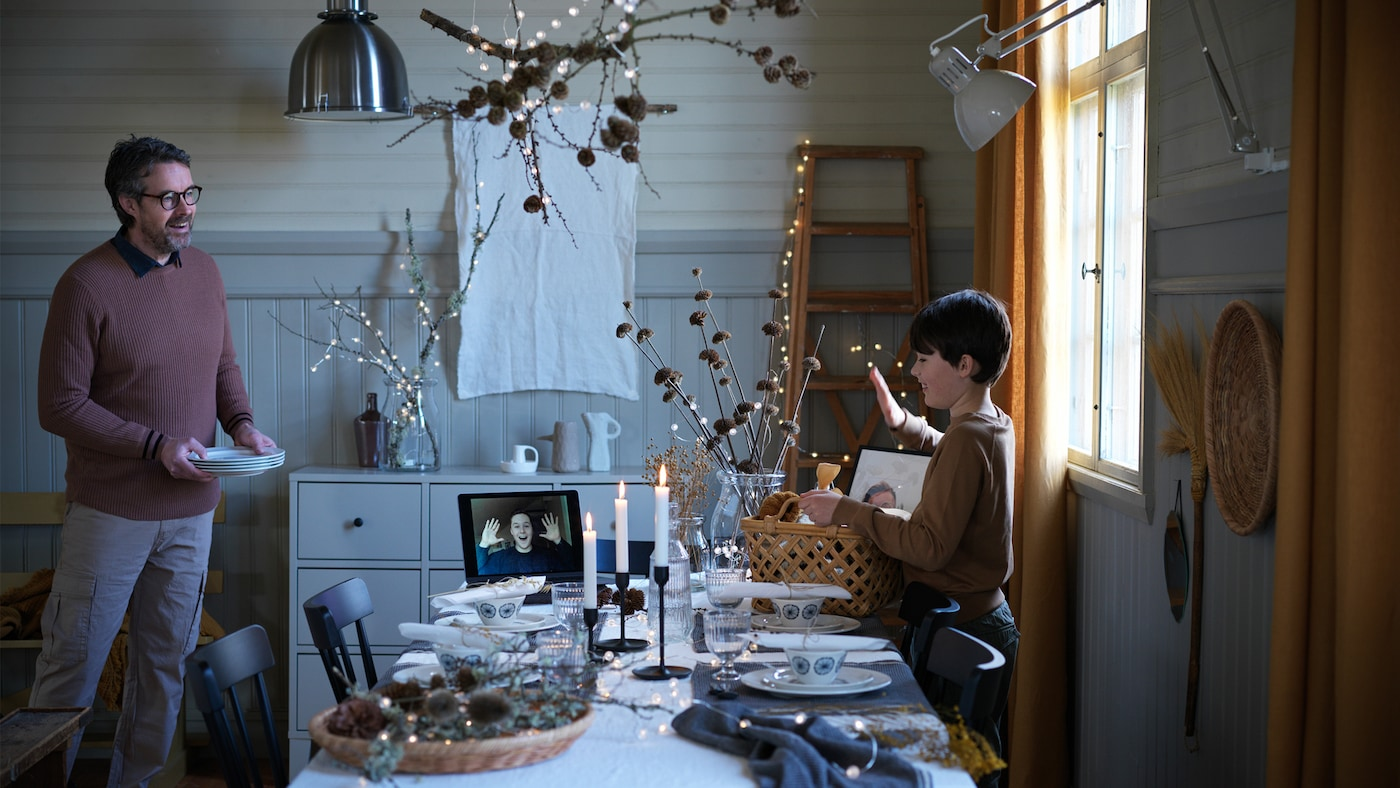 A boy waves to a person on a video call on a tablet in a candlelit festive dining room; the boy has a basket of gifts.