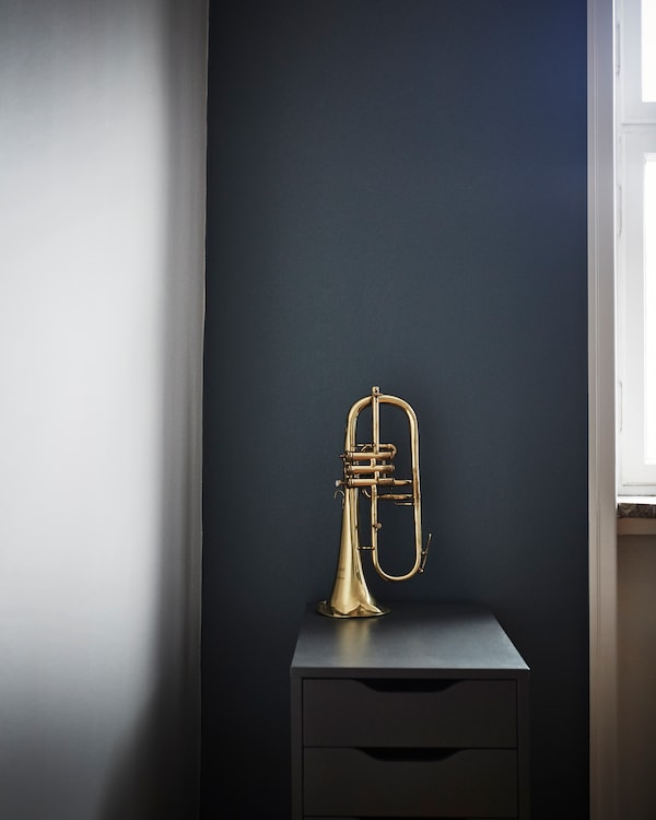 A brass trumpet sits on a drawer unit in front of a dark wall.