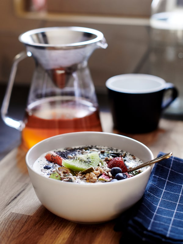 A breakfast bowl with yoghurt and fruit beside a tea pot, mug and checked blue napkin on a wooden table.