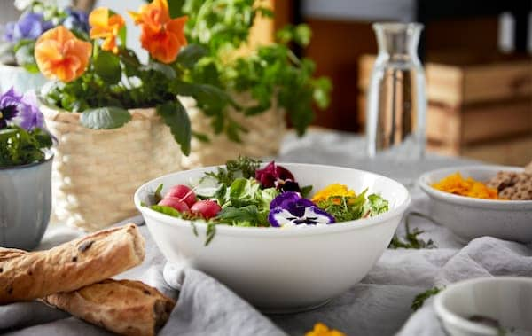 A breakfast table set with different kinds of bread, pot of flowers and a bowl of colourful garnished greens.