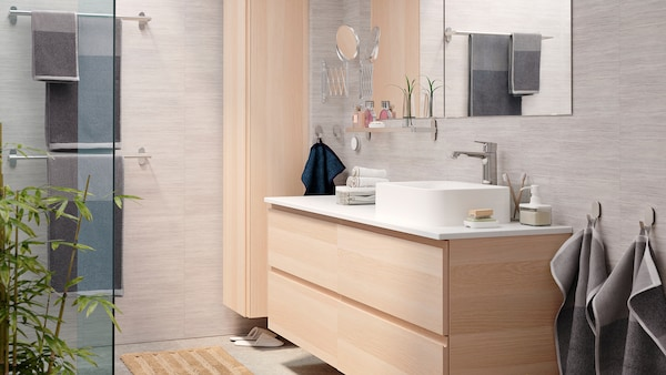 A bright and elegant bathroom with a GODMORGON wash-stand and GODMORGON high cabinet in white stained oak effect.