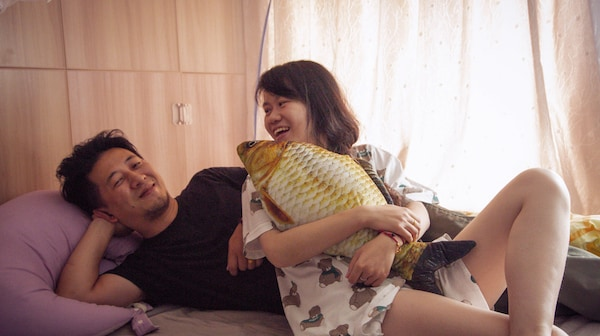 A bright bedroom and a young couple laughing while relaxing on the bed with a yellow fish-shaped pillow.