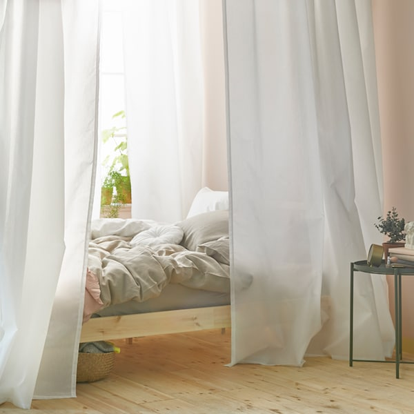 A bright bedroom with a bed near a window. The bed has a canopy of white curtains which hang from VIDGA curtain tracks.