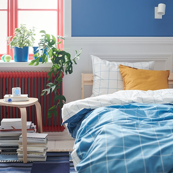 A bright bedroom with light blue and white bedding, a yellow cushion, and plants on a windowsill.