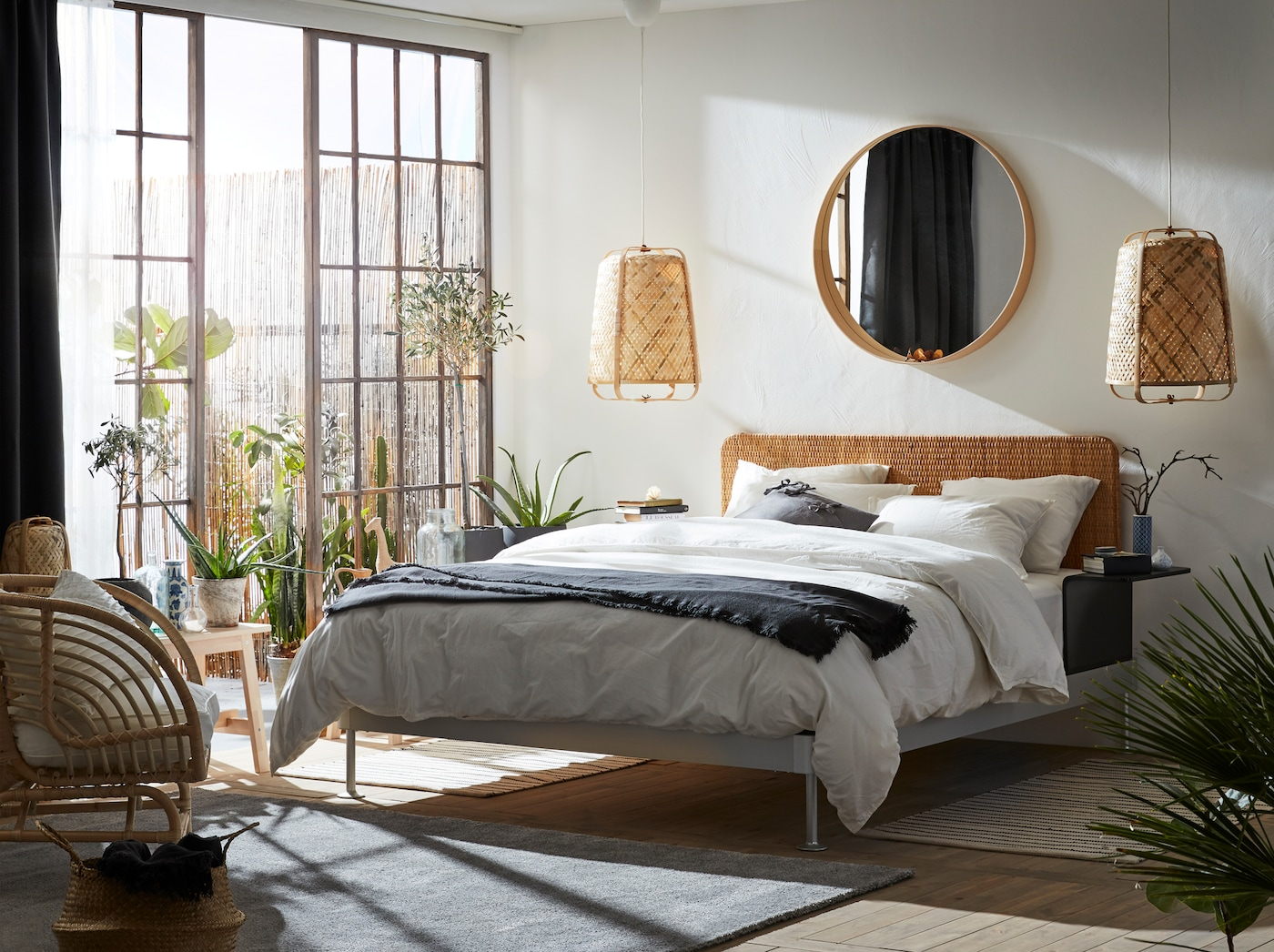 A bright bedroom with lots of natural materials, like rattan and bamboo. Big glass doors and an outdoor area next to the bed.