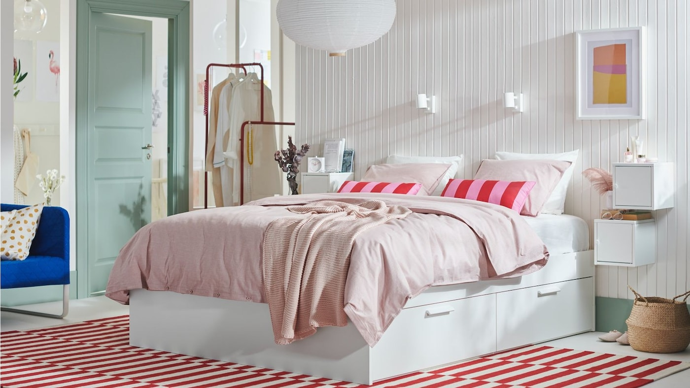 A bright, colourful bedroom with bed and storage drawers.