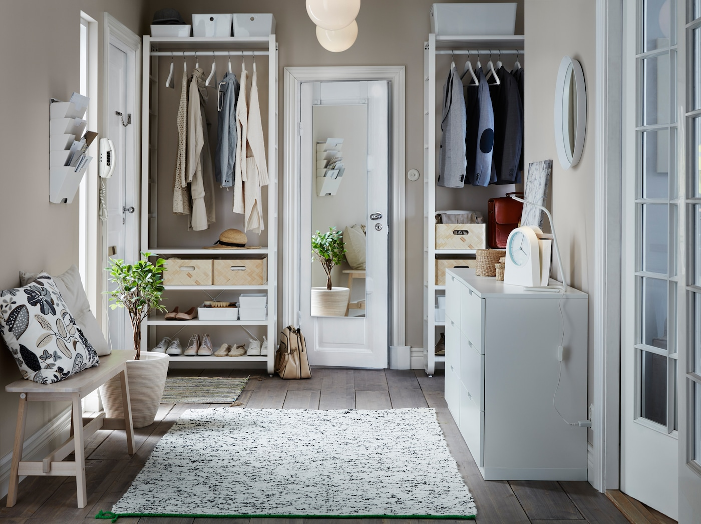 A bright hall with lots of storage space thanks to NORDLI cabinet and white ELVARLI clothes racks from IKEA.