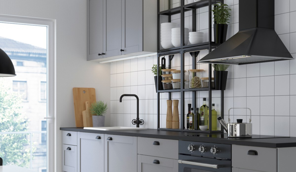 A bright kitchen featuring grey cabinets and drawers, white tile walls and open shelving.