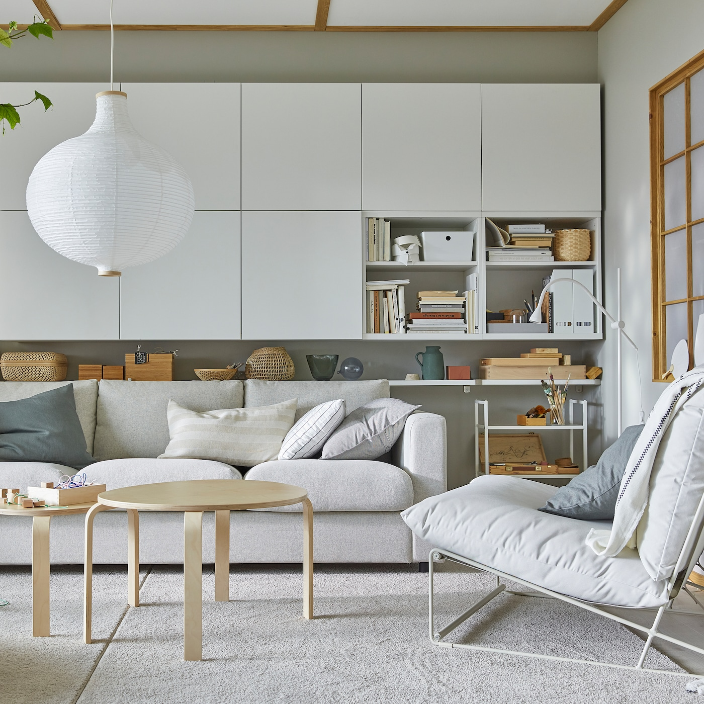 A bright living room with a HAVSTA easy chair, many white wall-mounted cabinets and a round, white pendant lamp.
