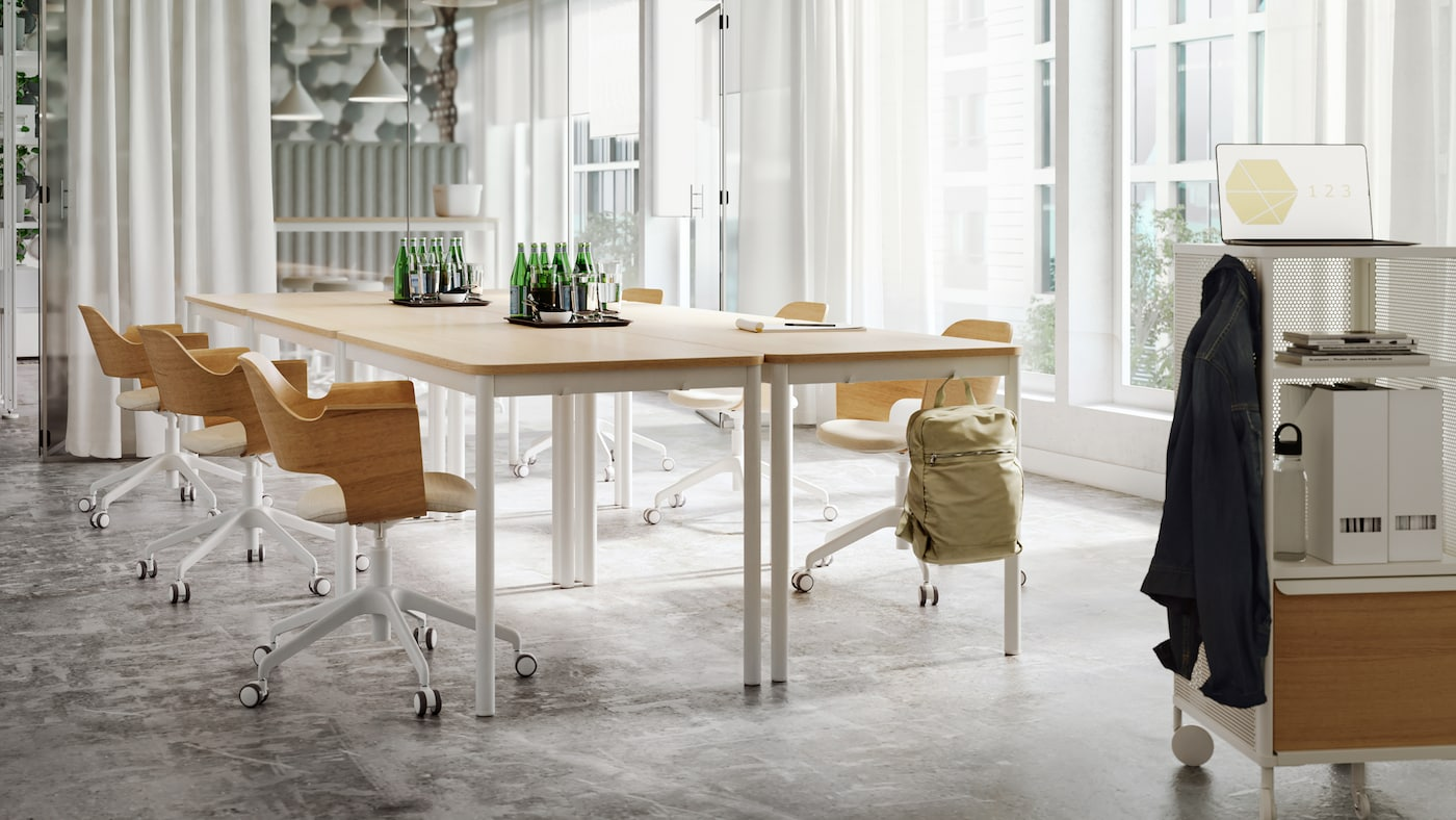 A bright meeting room with tables and chairs in light wood and white tones, sheer white curtains and a glass wall.