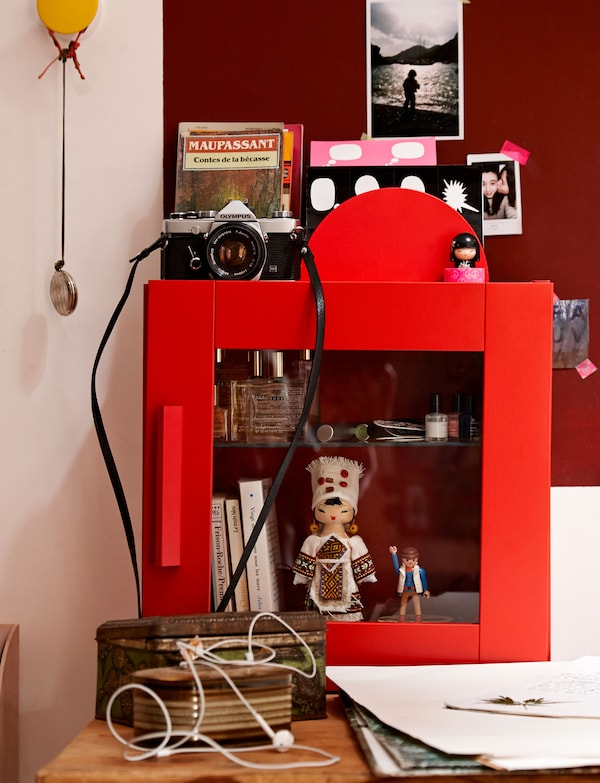 A bright red display box that shows off Lison's favourite tresures, including a doll, small books and nail polish.