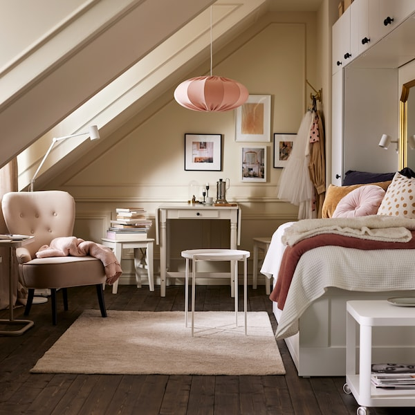 A bright room with a daybed, white wardrobes, a white tray table on a beige rug, a beige armchair and pink pendant.