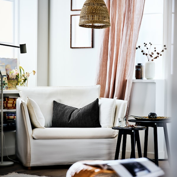 A bright, sunny living room corner containing a white BACKSÄLEN armchair beside a nest of coffee tables and a pink curtain.