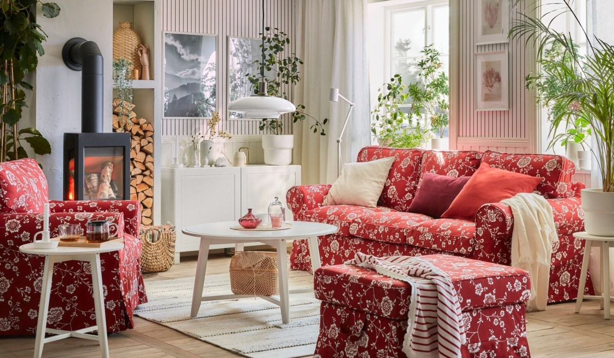 A bright, sunny living room with red fabric sofas, a footstool, and a white storage coffee table.