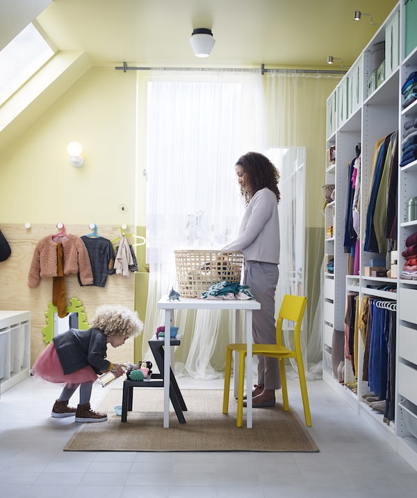 A bright utility room with open units to one side, a woman is sorting laundry on a table and a child is playing alongside.