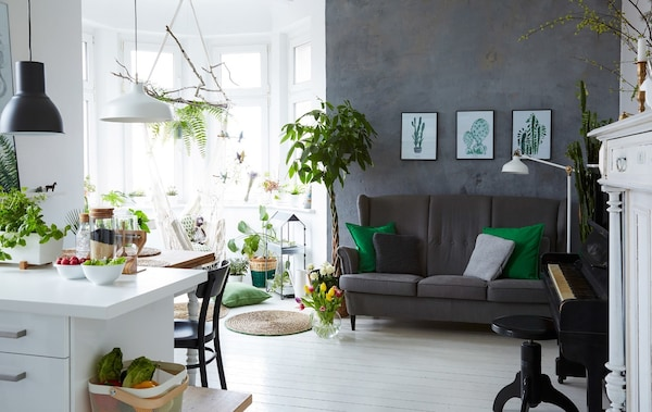 A bright, white kitchen that blends into the living room space where there's a grey sofa and grey wall.