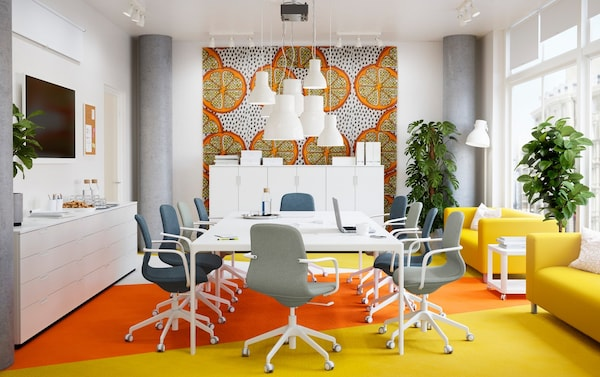 A bright yellow and orange conference room with long white BEKANT table and LÅNGFJÄLL blue and green swivel chairs.