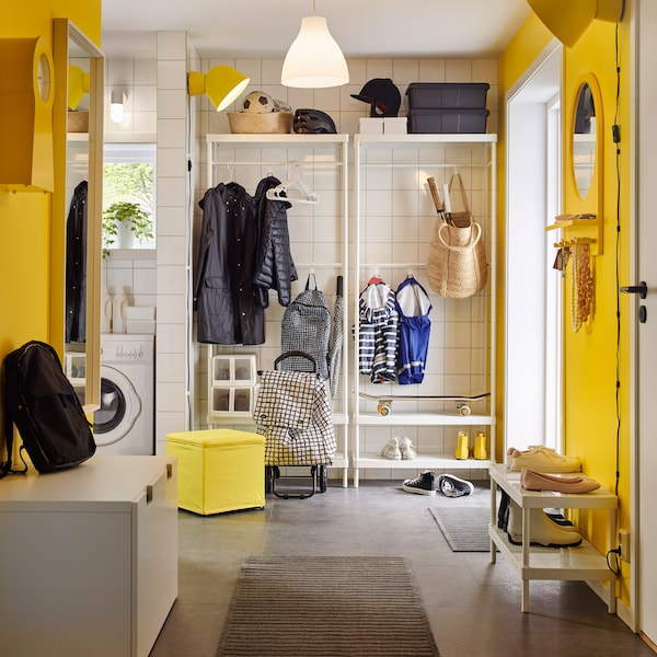 A bright yellow and white mudroom with a white coat and shoe rack.