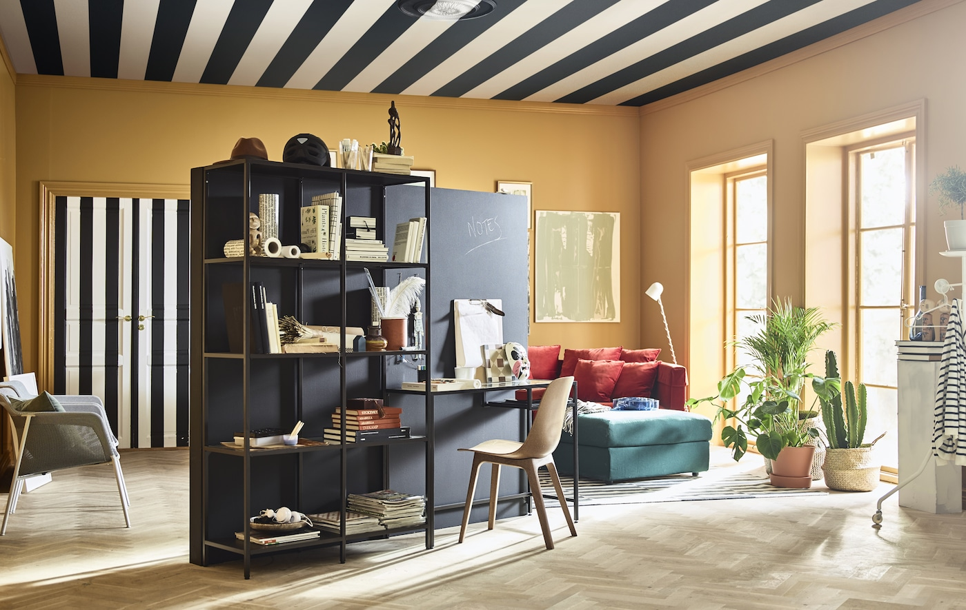 A brightly colored, creative living room is furnished with a stand-alone wall and work station in the center of the room.