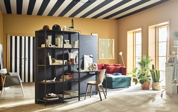 A brightly coloured, creative living room is furnished with a stand-alone wall and work station in the centre of the room.