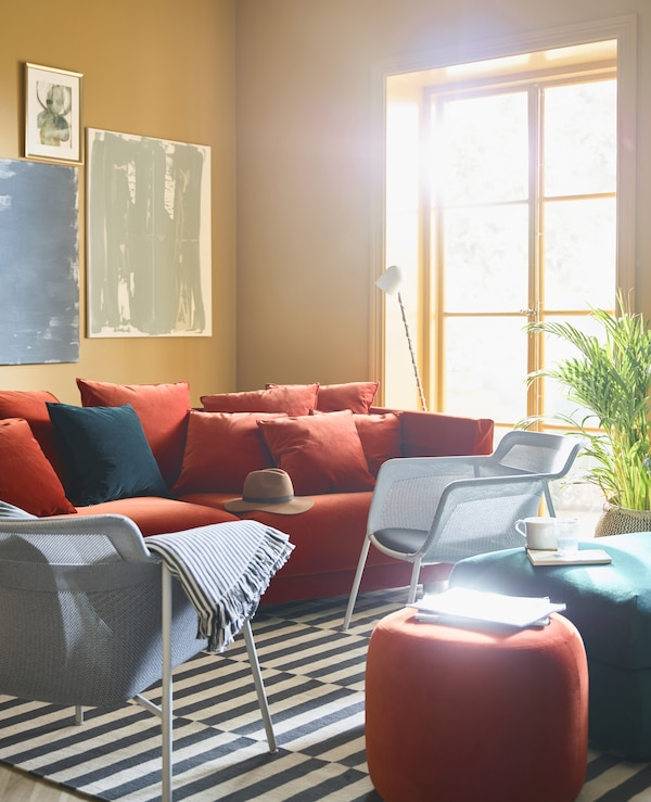 A brightly coloured living room with ochre walls is burnished with a red sofa and armchairs.