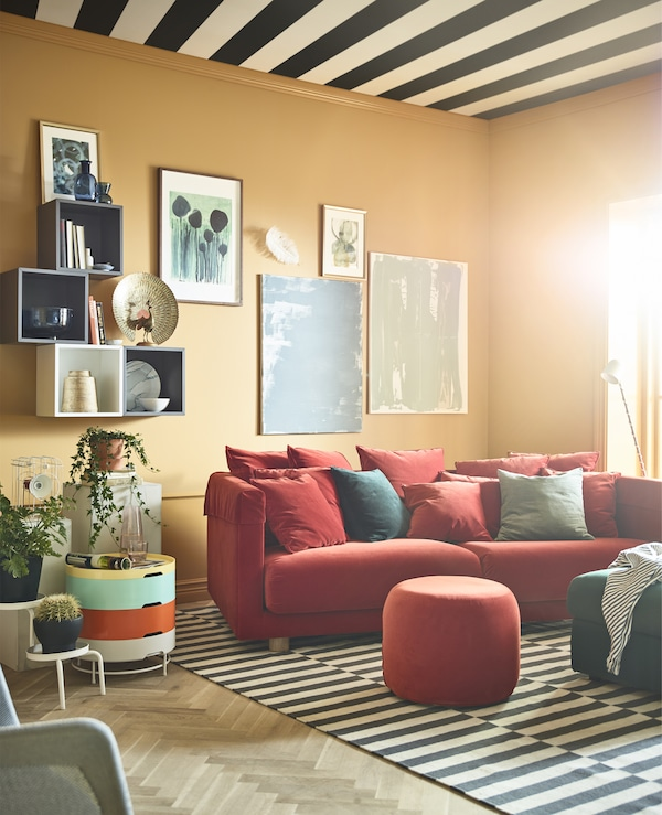A brightly coloured living room with ochre walls is burnished with a red sofa and ottomans.