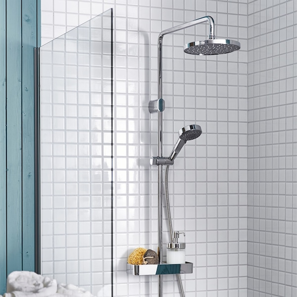 A BROGRUND shower in a white tiled bathroom, showing both the overhead shower head and the detachable handheld shower head.