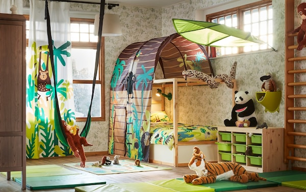 A brown and green jungle safari theme children's bedroom with KURA reversible bed and bed tent.