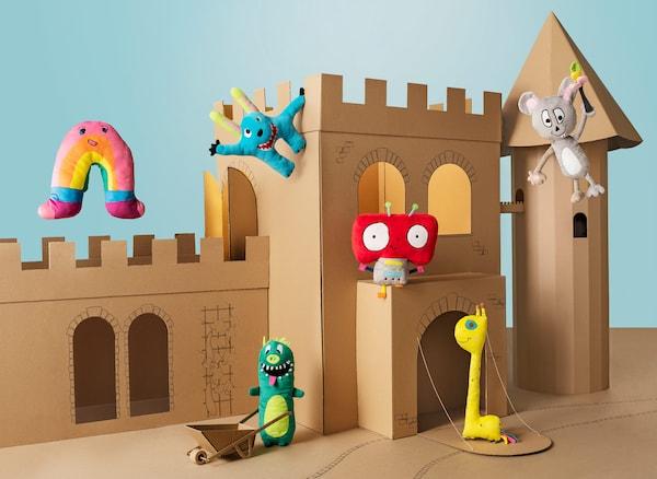 A brown cardboard castle serving as a backdrop for six colorful IKEA SAGOSKATT soft toys.