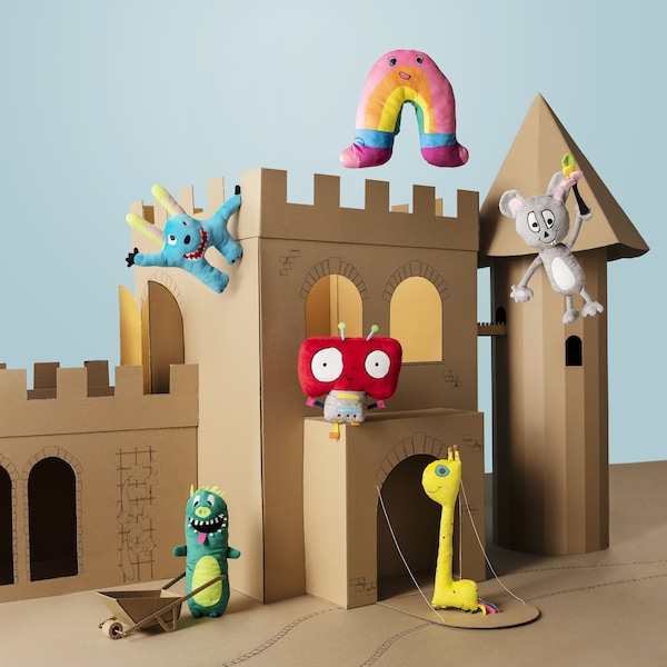 A brown cardboard castle serving as a backdrop for six colorful IKEA SAGOSKATT soft toys based on children's drawings.