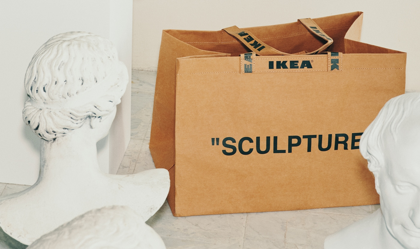 """A brown IKEA bag, with the word """"SCULPTURE"""" written on it, sits between two white sculptures."""