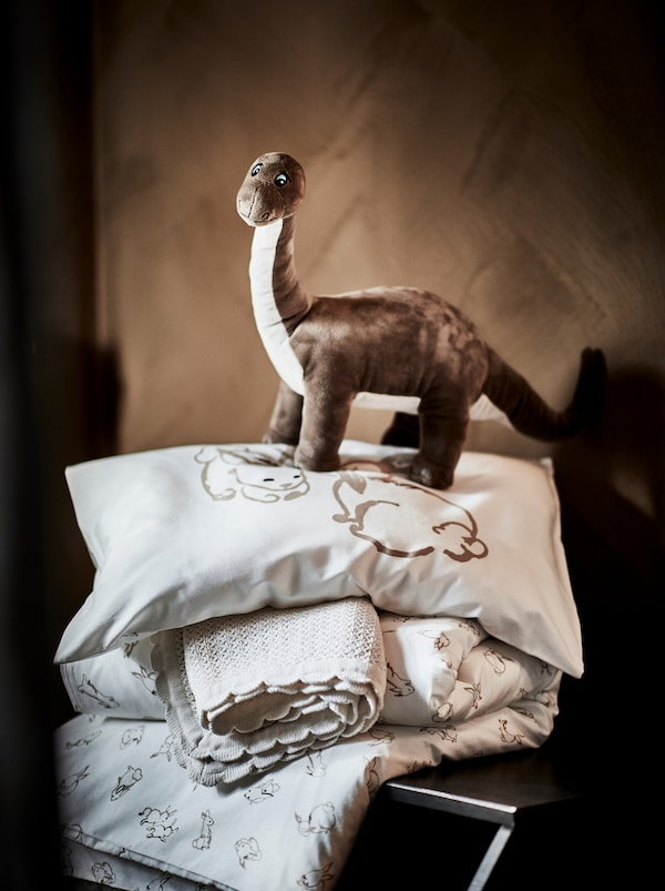 A brown JÄTTELIK soft dinosaur toy standing on top of a pillow and blankets with bed linen in soft natural tones.