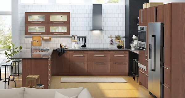 A brown kitchen with stainless steel appliances and wall cabinets with glass doors and interior lighting.