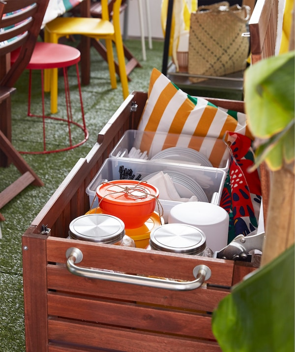 A brown stained IKEA ÄPPLARÖ storage bench made from acacia wood for outdoor use, filled with party supplies.