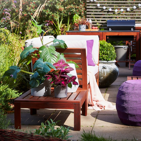 A brown-stained table with plants in grey plant pots and a white table lamp. A purple pouffe stands beside on the ground.