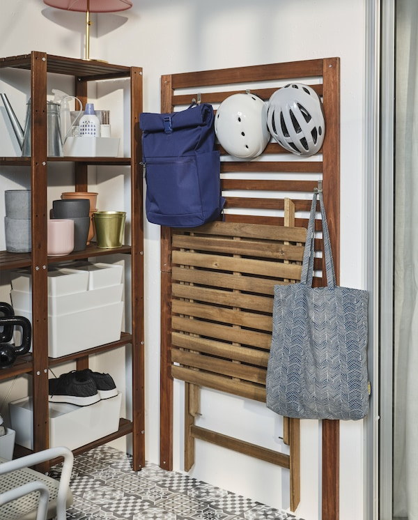 A brown-stained wall-mounted wall panel with hooks. A backpack, a tote bag, a folded table and two helmets hang on the hooks.