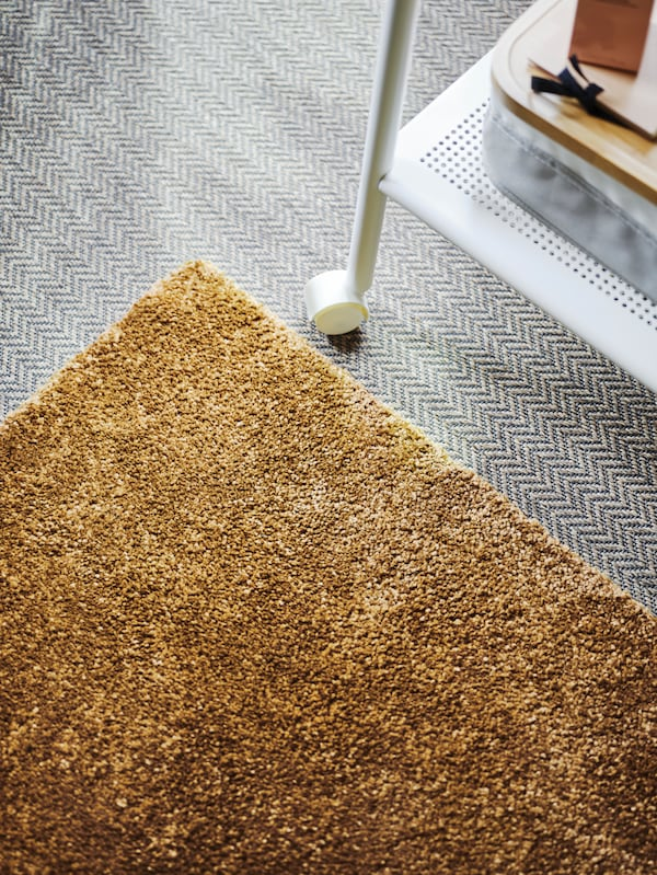 A brown-yellow STOENSE rug is placed on a gray floor, with a white metal rolling table alongside it.
