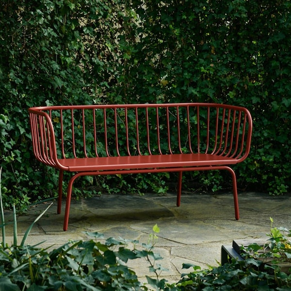 A BRUSEN 3-seat outdoor sofa in red, standing somewhere outdoors in paved ground and surrounded by greenery.