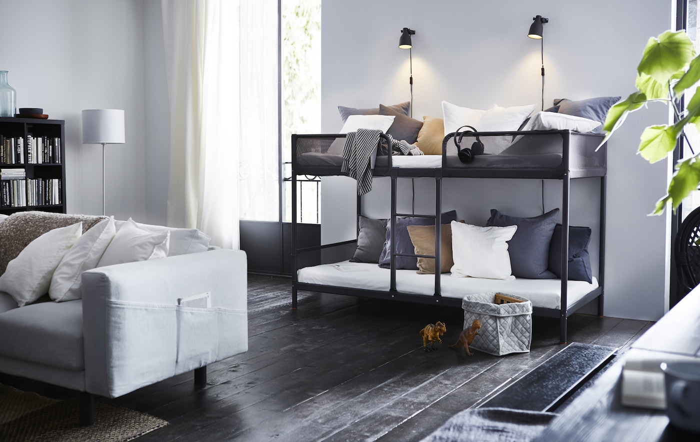 A bunk bed in a living room with gray and white pillows.
