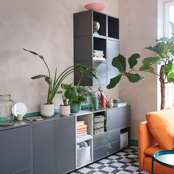 A cabinet combination in grey and white with shelves, drawers and doors. Green plants, books and decorative items stand here.