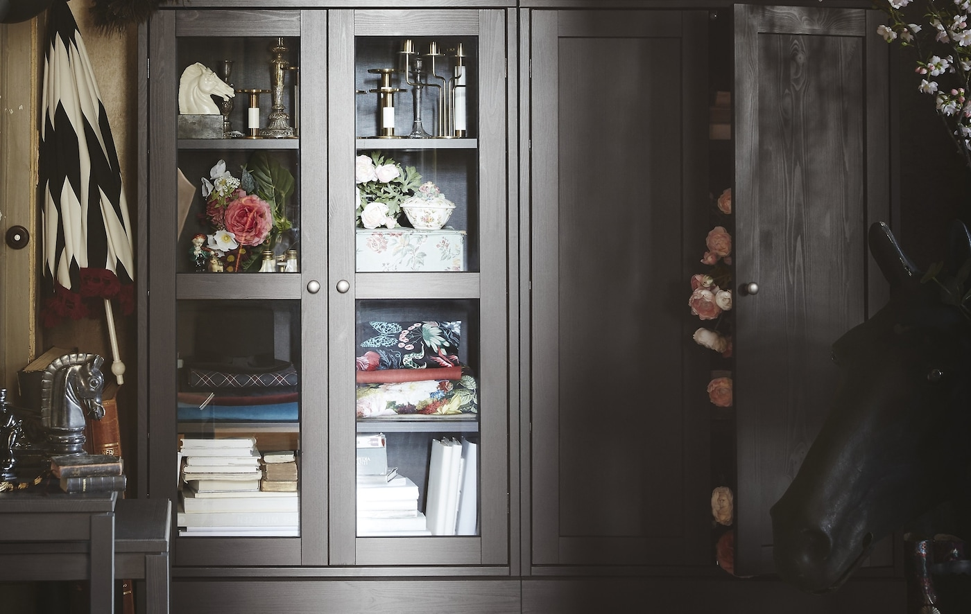 A cabinet with glass doors displaying various home decoration accessories and books.