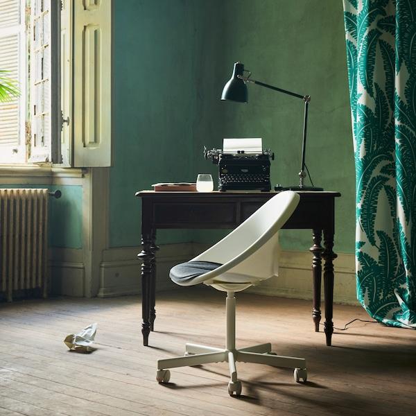 A cadeira giratória LOBERGET/BLYSKÄR em branco com um design arredondado, junto a uma secretária antiga, perto de uma janela aberta numa divisão verde.